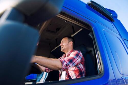 Professional middle aged trucker in cabin driving truck and smiling.