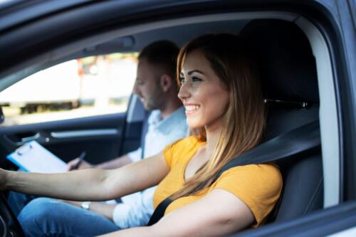 Close up view of female student driving a car and instructor holding checklist in background.