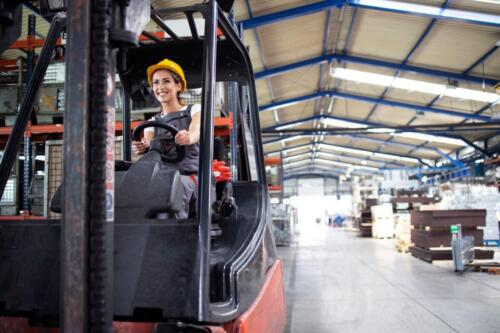 Professional female industrial driver operating forklift machine in factory's hall.